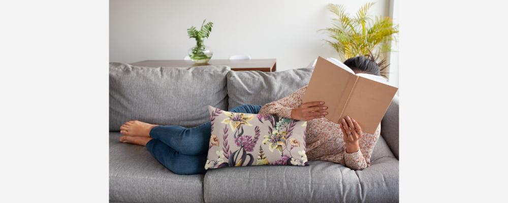 אישה שוכבת על ספה בצבע אפור נשענת על כרית נוי דגם מלינה וקוראת ספר